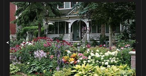 Queen Anne Victorian House colorful flower garden surrounding a queen anne victorian