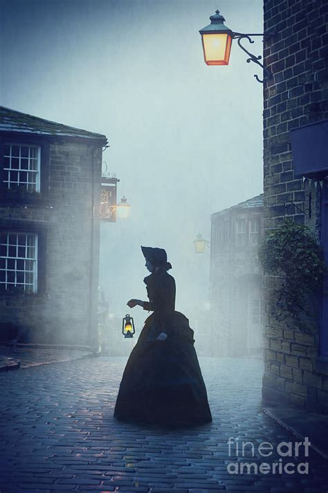 victorian woman with an oil lamp at night on a cobbled