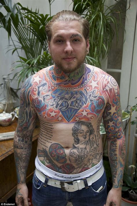 father who has tattoos over entire body including his lips