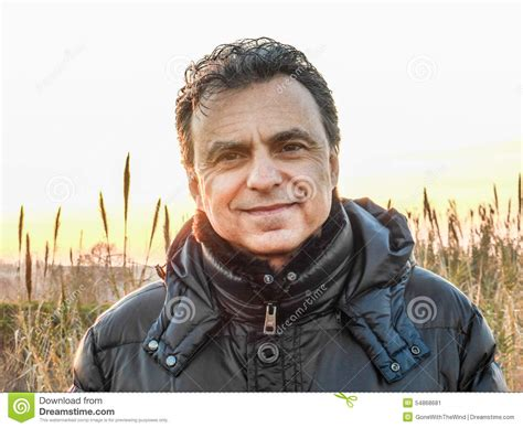 hair middle aged man dark elegant man with dark padded jacket in the countryside