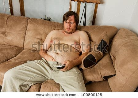 fat guy on couch fat obese man on the couch with remote in one hand and the