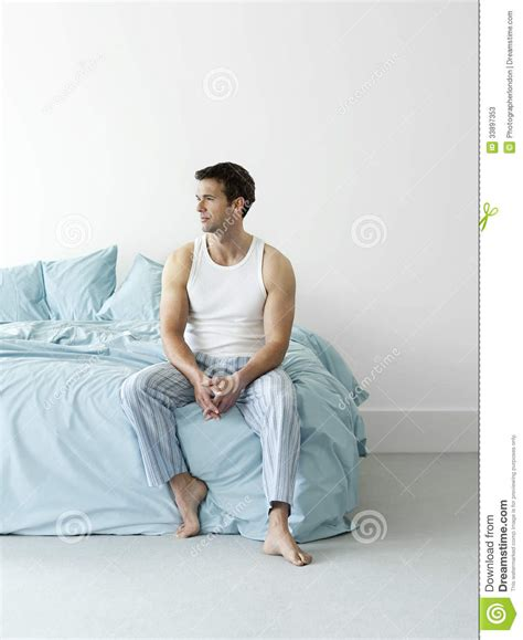 thoughtful man in nightwear sitting in bed stock photos