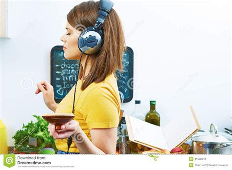 vrouw in keuken vrouw in keuken het koken met het luisteren muziek stock