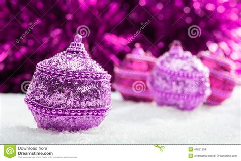 pink and purple christmas balls in snow stock photo
