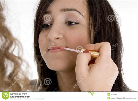 portrait of teenage girl putting lipstick on while looking at her beautiful teen having makeup put on her stock photo