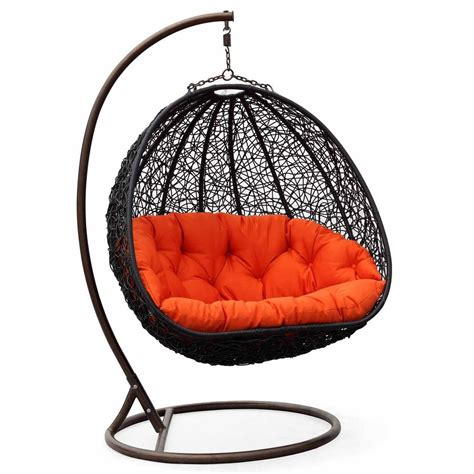 the swing chair two can curl up in this dual sitting outdoor wicker swing