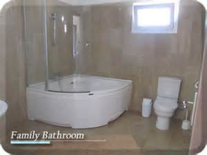 a large bathroom having a white suite featuring a corner kudos inspire over bath shower panel 1556 x 350mm with