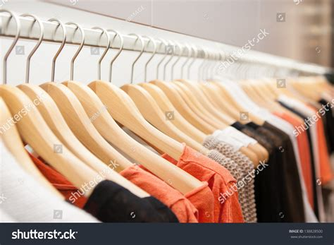 clothes hang on a shelf in a designer clothes store in