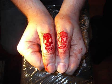 tattoo scarification process skull scarification matching tattoos on both thumbs by