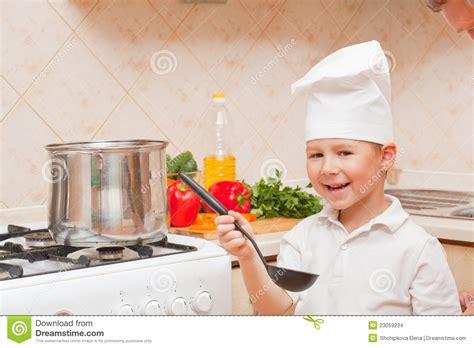 les gar輟ns dans la cuisine petit gar 231 on sur la cuisine images stock image 23059234