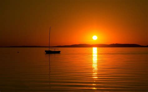 sunset silhouette boat sea golden hour reflection