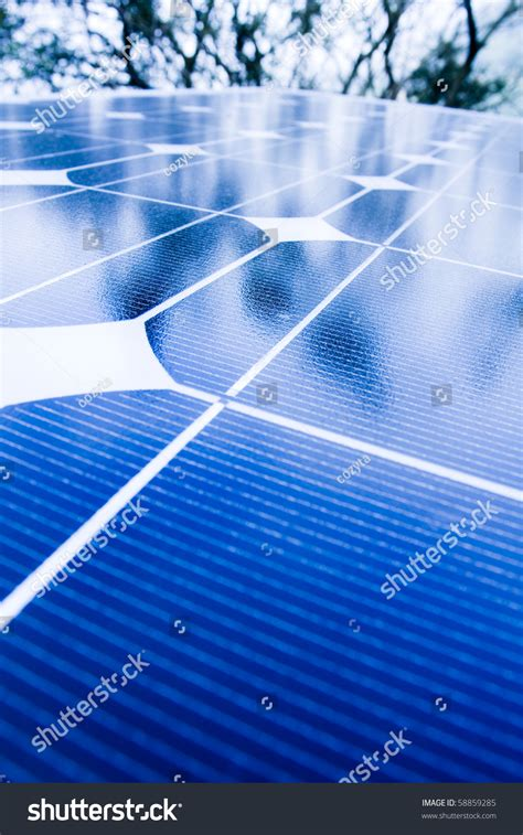 green trees and blue sky reflection on solar panels go