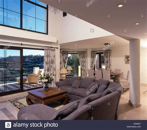 double height living room grey l shaped sofa in modern double height spanish living
