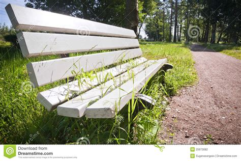 white park bench white park bench with grass growing through stock photo image of object road 25973082