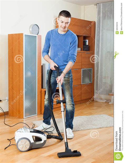 vacuum the living room in cleaning with vacuum cleaner in living room stock photo image 63518416