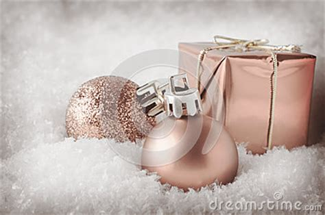 pale pink christmas decorations in snow stock photo