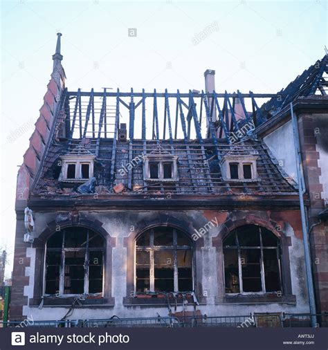 buying a fire damaged house ruined house after fire damage with burned out roof framework stock photo royalty