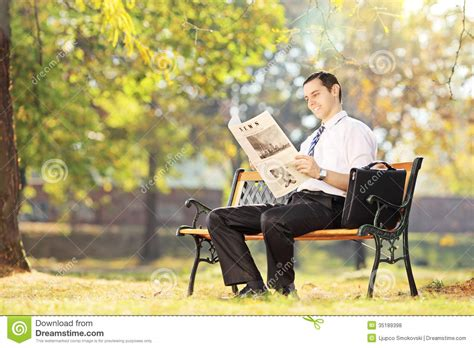 bench reading young smiling man seated on bench reading newspaper in a park royalty free stock