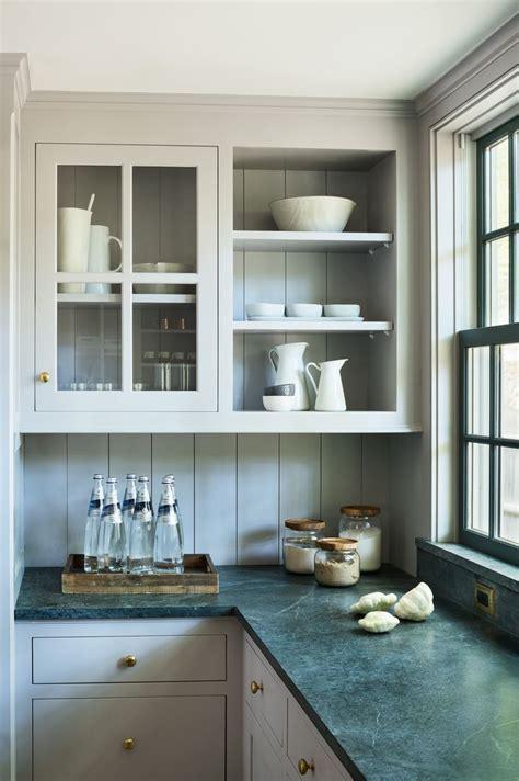 Green colored countertops, cream colored kitchen cabinets