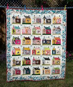 house quilt with family pictures in the windows and doors