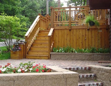 wood deck with brick paver patio and retaining wall