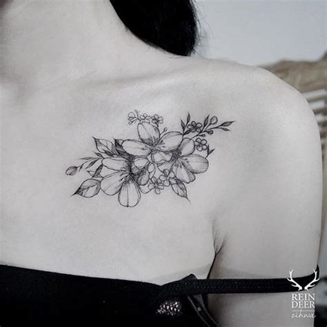 small cute blackwork style collarbone tattoo of flowers by