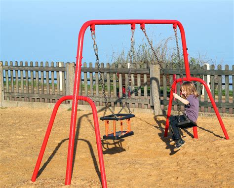 swing around fun time child playing on a swing in a playground stock photo