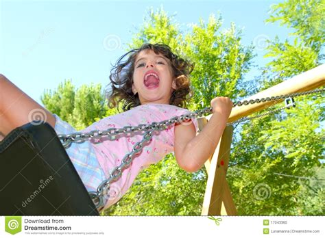 girl swing girl swinging on swing happy in trees outdoor stock photo
