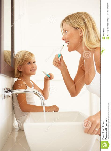 mom in bathroom mother and daughter brushing teeth in bathroom stock photo