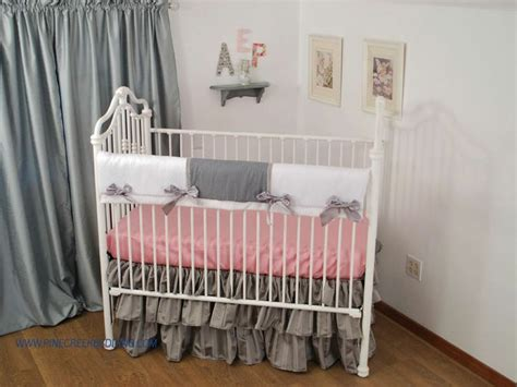 white grey crib rail guard with a pink sheet and 3 tier
