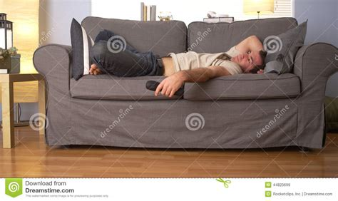 having on couch man trying to sleep on couch stock photo image 44820699