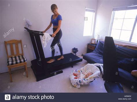treadmill in bedroom mother running on treadmill in bedroom with baby stock