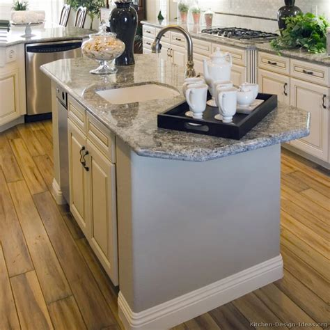 Kitchen Sink Island | antique white kitchen with wood floors and an island sink