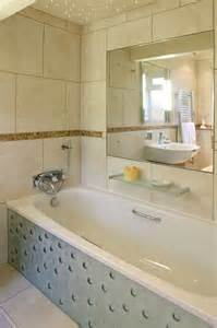 Unique glass bath panel with tiled walls and inset mirror
