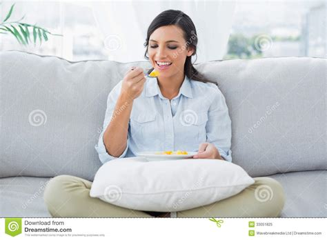 woman grows into couch cute woman sitting on the couch crossing legs eating