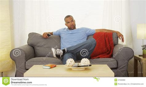 couch sitting black man sitting on couch watching tv stock photo image