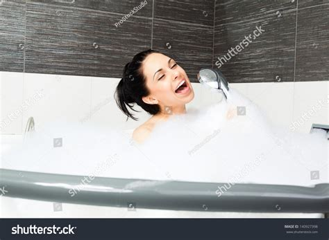 singin in the bathtub beautiful woman singing bath smile young stock photo