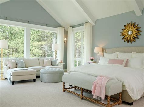 chic blue bedroom features a gold sunburst mirror a
