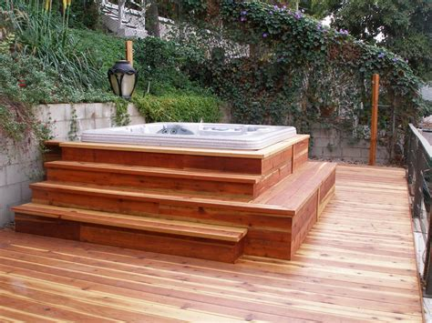outdoor hot tub above wooden deck hot tub with stairs surrounded by lush