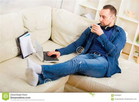 having on the sofa gut aussehender mann der auf sofa mit tasse tee sitzt