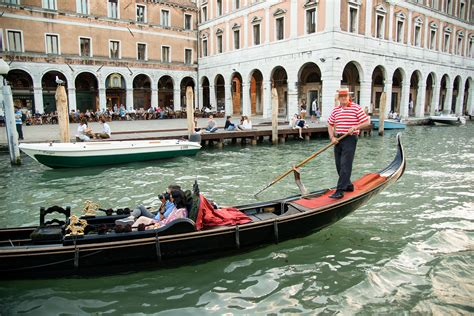 boats in italy called file gondolier on the grand canal venice italy jpg