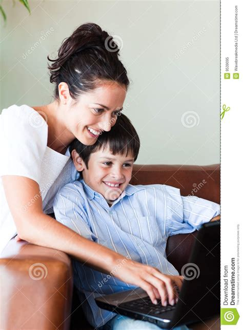 the last mama on the couch play mother and son playing with a laptop royalty free stock