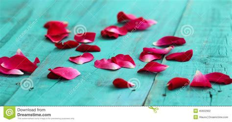 Red Rose Petals Scattered On Antique Teal Blue Wooden