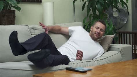jumping on the sofa man jumping relaxing on sofa stock footage video 6456689