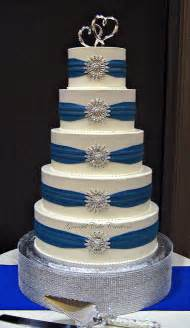 royal blue and silver wedding white buttercream wedding cake with royal blue sashes and silver brooches a photo on
