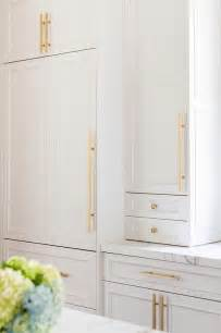White Cabinets With Antique Brass Hardware White Cabinets Adorned With Long Brass Pulls And Brass