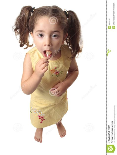 tiny small little girl eating a lollipop candy royalty free stock