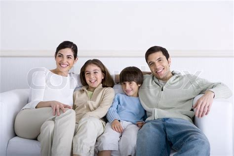 family sofa family sitting together on sofa smiling stock photo