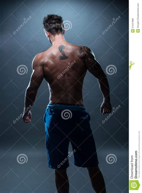back view of a athletic man with tattoo stock