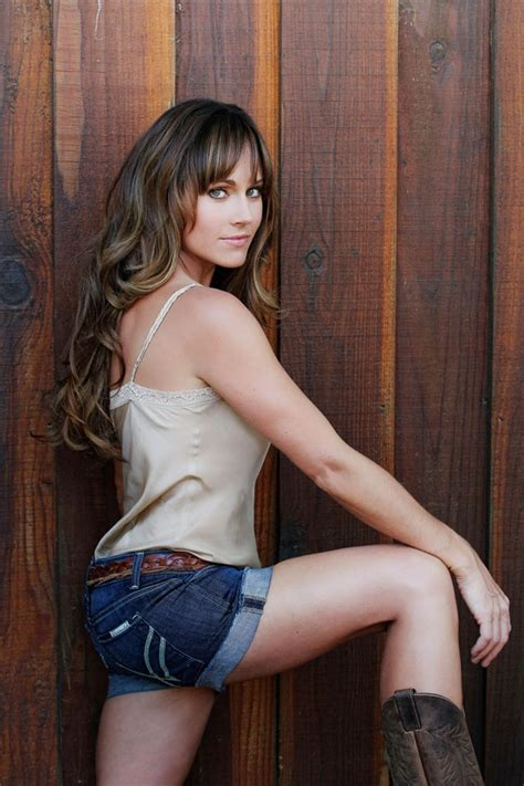 nikki deloach from the side in a cream tank top and jean